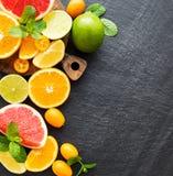 Fresh citrus fruits. On a black stone background stock photography