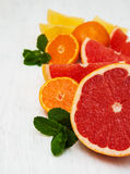 Fresh citrus fruits with green mint. On a old white wooden background Royalty Free Stock Photo