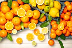 Fresh citrus fruits with leaves on wooden background. Copy space for text stock images