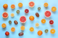 Fresh citrus fruits split on turquoise background. royalty free stock photo