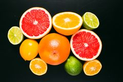 Fresh citrus stihli. Lemons, limes, grapefruit and orange on a black background.  stock images