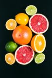 Fresh citrus stihli. Lemons, limes, grapefruit and orange on a black background.  royalty free stock photos