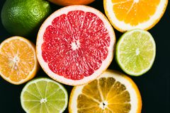 Fresh citrus stihli. Lemons, limes, grapefruit and orange on a black background.  royalty free stock photography