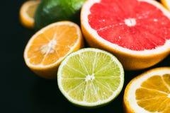 Fresh citrus stihli. Lemons, limes, grapefruit and orange on a black background.  Royalty Free Stock Image