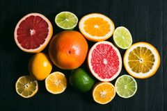 Fresh citrus stihli. Lemons, limes, grapefruit and orange on a black background.  royalty free stock image