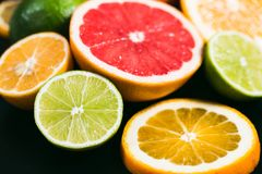 Fresh citrus stihli. Lemons, limes, grapefruit and orange on a black background.  stock photo