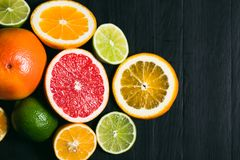 Fresh citrus stihli. Lemons, limes, grapefruit and orange on a black background.  royalty free stock images
