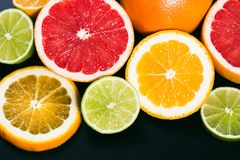 Fresh citrus stihli. Lemons, limes, grapefruit and orange on a black background.  stock photography