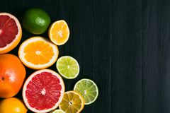 Fresh citrus stihli. Lemons, limes, grapefruit and orange on a black background Royalty Free Stock Photography