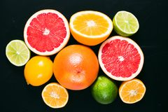 Fresh citrus stihli. Lemons, limes, grapefruit and orange on a black background.  royalty free stock photo