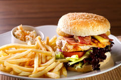 Hamburger. Fresh classic american hamburger sandwich with french fries and sauce on side Royalty Free Stock Image