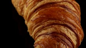 Fresh classic croissant. Baked French classic croissant on black background stock video
