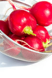 Fresh clean radishes. Fresh clean red  radishes in a strainer over a white background Stock Photo