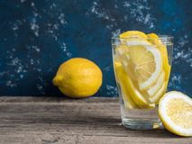 Fresh clean water in a glass with slices of lemon. Lemonade on wooden table and blue background. Living water, healthy drink.  royalty free stock image