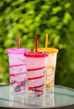 Fresh Clean Water and Ice inside of colorful cups with matching Royalty Free Stock Photo
