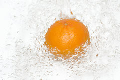 Fresh, clean water splash on a juicy orange. Royalty Free Stock Image