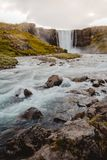 Fresh clean waterfall Gufufoss near Seydisfjordur in Iceland in summer with loads of water flowing between rocks, snow in the. Background - film look, vertical royalty free stock images