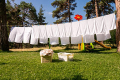 Fresh clean white towels drying on washing line. In outdoor stock photo
