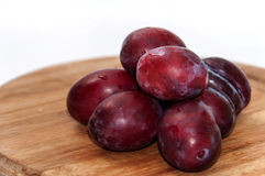 Fresh cleaned plums on the kitchen wooden board Stock Images