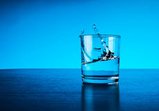 Fresh clear blue water splash in glass Stock Photography