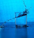 Fresh clear blue water splash in glass Stock Image
