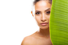 Fresh clear face. Pretty fresh clear face of young woman behind green leaf isolated on white Royalty Free Stock Photo
