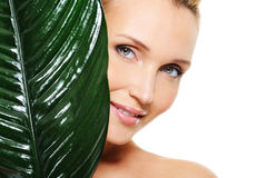 Fresh clear face of young woman behind the plant stock photo