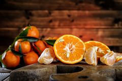 Fresh clementines freshly picked in slices and in wedges on wood Stock Photos