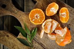 Fresh clementines freshly picked in slices and in wedges on wood Royalty Free Stock Photo