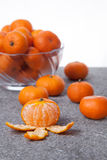 Fresh Clementines fruit peeled with glass bowl in vertical. Picture of Fresh Clementines fruit peeled with glass bowl in vertical Stock Photo