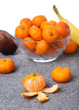 Fresh Clementines fruit peeled with glass bowl in vertical. Picture of Fresh Clementines fruit peeled with glass bowl in vertical Royalty Free Stock Images