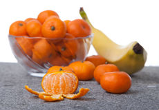 Fresh Clementines fruit peeled with glass bowl in vertical. Picture of Fresh Clementines fruit peeled with glass bowl on grey stone Stock Images