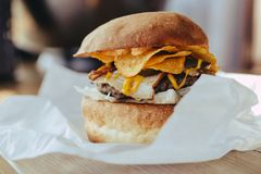 Fresh close-up of designer homemade burger with cutlet, bacon, chips and mustard sauce in craft paper on a wooden table royalty free stock photography