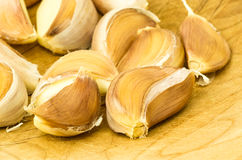 Fresh cloves of garlic on wooden board Stock Images