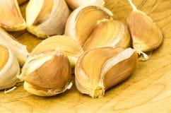 Fresh cloves of garlic on wooden board. Fresh cloves of garlic on wooden cutting board Stock Images