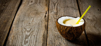 Fresh cocktail in coconut cup on wooden background. Free space for text. Royalty Free Stock Photo