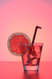 Fresh cocktail with grapefruit, ice and striped drinking straw. Stock Image