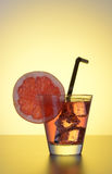 Fresh cocktail with grapefruit, ice and striped drinking straw. Royalty Free Stock Photos