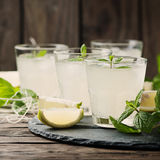 Fresh cocktail with lemon, ice and mint on the vintage table Stock Photos