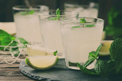 Fresh cocktail with lemon, ice and mint on the vintage table Royalty Free Stock Photo