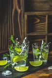 Fresh cocktail with lime, ice and rosemary, mojito cocktail in a bur on a rustic table. Selective focus, shallow depth of the field stock photos