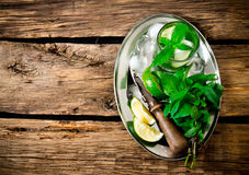 Fresh cocktail of lime, mint, rum and ice on a metal tray . On a wooden table. Free space for text . Stock Image