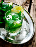 Fresh cocktail of lime, mint, rum and ice on a metal tray . On a wooden table. Royalty Free Stock Photography