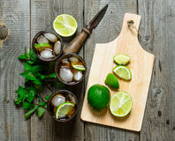 Fresh cocktail with lime and mint on wooden table. Royalty Free Stock Photos