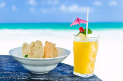 Fresh cocktail with orange juice and nachos on table at tropical exotic Caribbean beach Royalty Free Stock Images