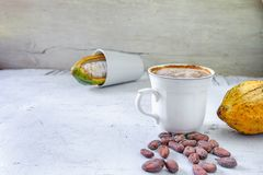Fresh cocoa fruit and hot cocoa cup royalty free stock photography
