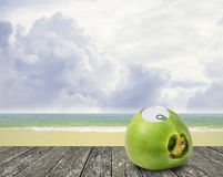 Fresh coconut with can open tool on top and beach location Stock Image