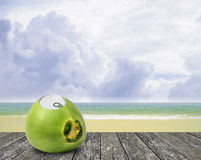 Fresh coconut with can open tool on top and sea background Royalty Free Stock Images