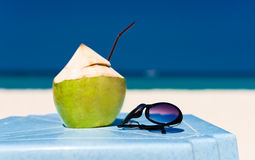 Fresh coconut cocktail and blue sunglasses Stock Image