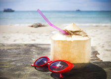 Fresh coconut cocktail and red sunglasses on the beach. Fresh coconut cocktail and red sunglasses on tropical beach Stock Photography